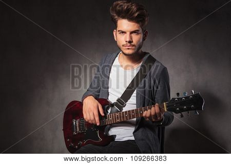 portrait of fashionable artist playing guitar while sitting in dark studio background