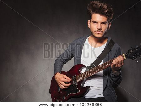 portrait of sexy man playing guitar while looking at the camera