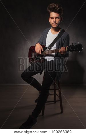 sexy fit artist playing guitar in studio while sitting and looking at the camera