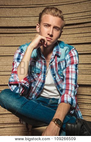 young handsome man sitting in studio legs crossed while touching his chin