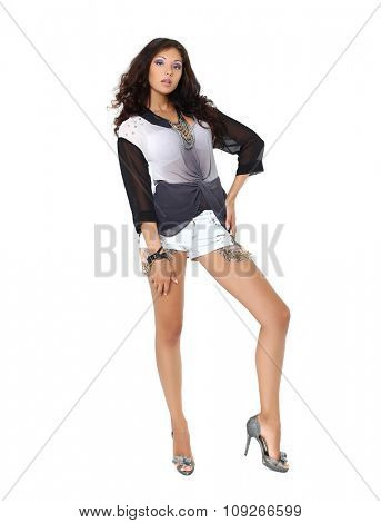 Beautiful model in a fashionable blouse and short jean shorts posing on white background