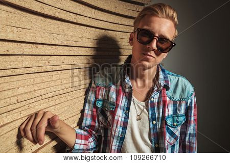 portrait of blonde skinny man wearing sunglasses while leaning against the wooden studio wall