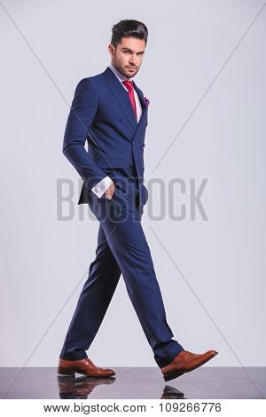 serious man in business suit pose while walking with hands in pockets
