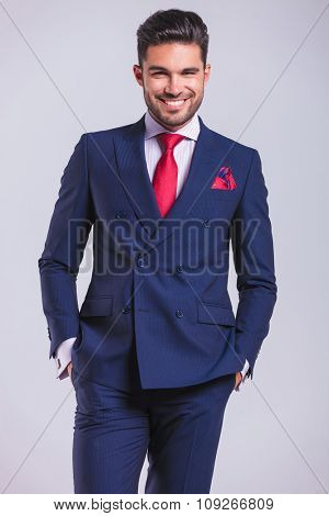 portrait of smiling business man posing with hands in pockets