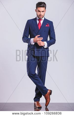 full body picture of handsome man in suit with legs crossed while touching hands