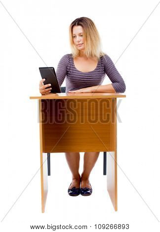 front view of woman sits by the table and looks at the screen of the tablet.    Isolated over white background. front view of a girl behind office desk reading an e-book.