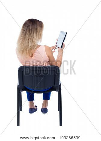 back view of woman sitting on chair and looks at screen of tablet.  Rear view people collection. Isolated over white background. Blonde in blue trousers sitting on the office chair and read e-books