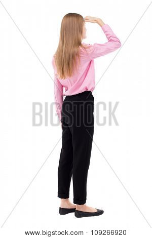 back view of standing young beautiful  woman.  girl  watching. Rear view people collection.  girl office worker in black trousers stands sideways and looks thoughtfully left put her hand to her eyes.