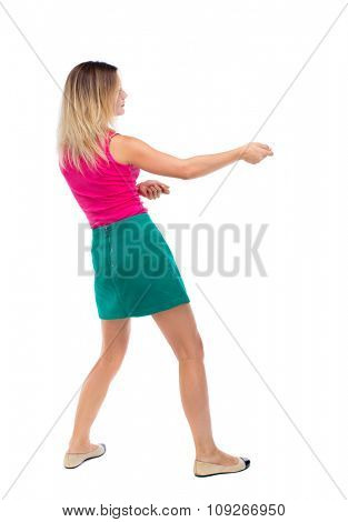 back view of standing girl pulling a rope from the top or cling to something. girl  watching. Rear view people collection.  . The blonde in a green skirt and pink sweater leaning legs pulls the rope.