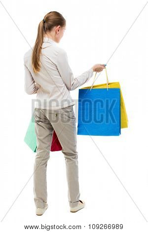 back view of woman with shopping bags . beautiful brunette girl in motion.  backside view of person.  Isolated over white background. Girl in gray jeans holding at arm's length paper bags.