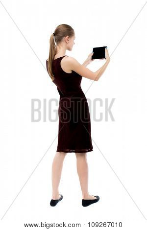 back view of standing young beautiful girl with tablet computer in hands of. girl  watching. Isolated over white background. The blonde burgundy dress holding to a horizontal smartphone