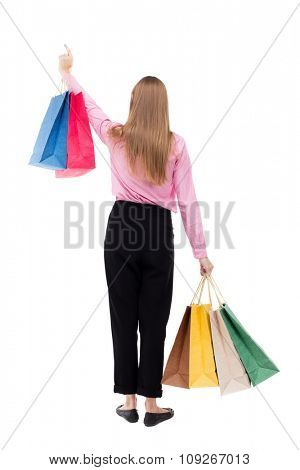 back view of woman with shopping bags. beautiful brunette girl in motion. Isolated over white background. girl in pink shirt stands with colorful shopping bags and showing thumb up.