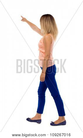 back view of pointing walking  woman. going girl pointing.  backside view of person.  Rear view people collection. Isolated over white background. The blonde is left in blue pants.