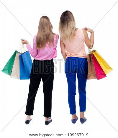 back view of  two women  with shopping bags. backside view of person.  Rear view people collection. Isolated over white background. Two blonde girls with colorful shopping bags looking up.
