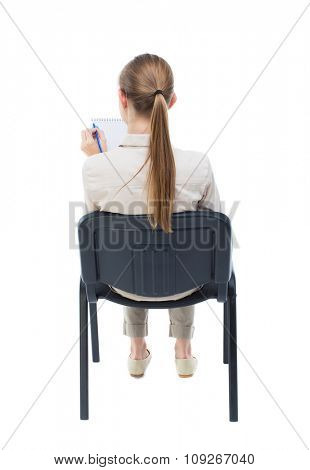 back view young beautiful woman sitting on chair. girl watching. Rear view people collection. Isolated over white background. Girl with long hair in white jacket is sitting on hair writing in notebook