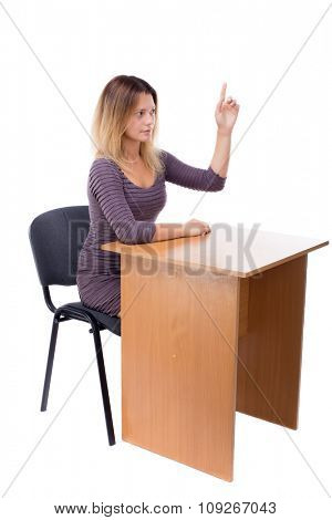 Woman sitting at the table and workingt. The girl behind the wooden table in the office. Isolated on white background. Blonde in a short dress sitting at a table holding up his hand for a question.