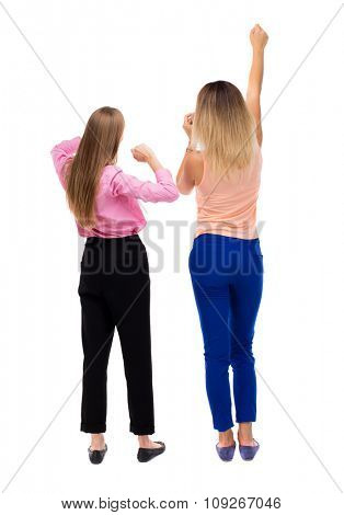 Back view of two young  women dancing.  Rear view people collection.  backside view of person.  Isolated over white background. Two girls blonde on the concert raised their hands.