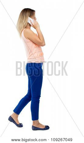 side view of a woman walking with a mobile phone. back view ofgirl in motion.  Rear view people collection. Isolated over white background. Blonde in blue trousers side is talking on the white phone.