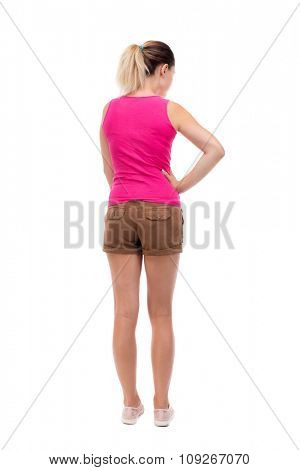 back view of standing young beautiful  woman.  girl  watching. Rear view people collection.  Blonde girl in shorts and a pink blouse is resting his hand in his right side. and looking up.