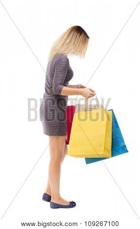 back view woman with shopping bags. beautiful brunette girl in motion. backside view person Rear view people collection. Isolated over white background. Girl in short dress looking into shopping bags.
