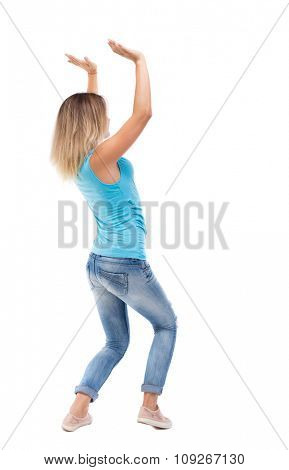 back view of woman  protects hands from what is falling from above.  backside view of person.  Isolated over white background. blonde in a blue t-shirt and jeans holding something heavy overhead.