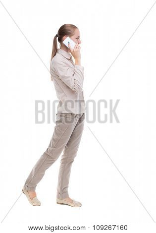 side view of a woman walking with a mobile phone. back view ofgirl in motion.  Rear view people collection. Isolated over white background. girl in a white jacket is talking on a white smartphone.