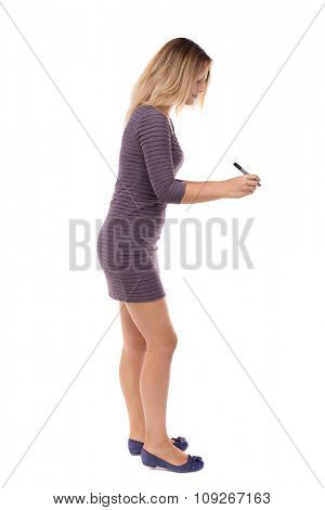 back view of writing beautiful woman. Rear view people collection.  backside view of person. Isolated over white background. Blonde in a short dress draws a felt-tip pen in front of him.