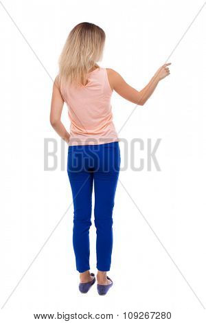 Back view of  pointing woman. beautiful girl. Rear view people collection.  backside view of person.  Isolated over white background. blonde in blue trousers is showing the right hand side.
