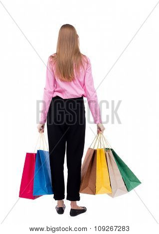 back view of woman with shopping bags . beautiful brunette girl in motion. . Isolated over white background. girl in pink shirt stands with lots of shopping bags and looking in front of him.