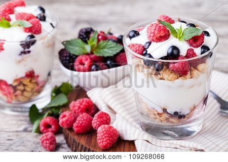 yogurt with muesli and berries on a wooden table