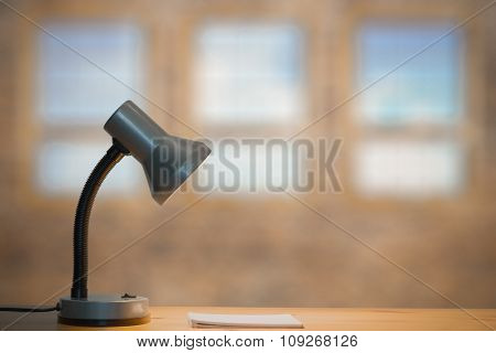 lamp and notebook on table in old room with big windows