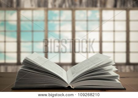 open book on wooden table in old room with big windows