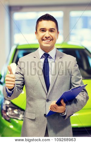 auto business, car sale, consumerism, gesture and people concept - happy man showing thumbs up at auto show or salon