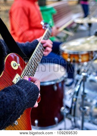 Music street performers on autumn outdoor. Middle section of body part. Hands with guitar on foreground.
