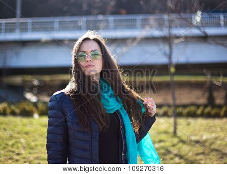 Young pretty woman with blue scarf posing in downtown