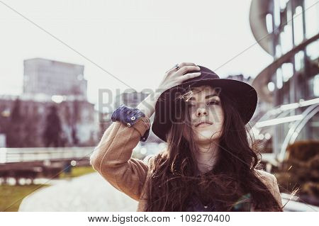 Young pretty woman posing in hat at downtown