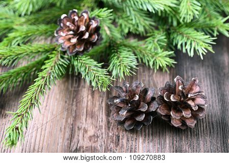 Fir Tree Twigs With Three Cones On Old Wooden Table