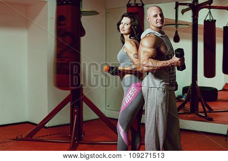Portrait Of A Man And Woman With Dumbbells In The Fitness Room