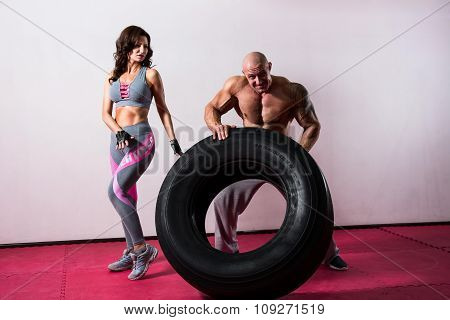 Crossfit Training. Woman And Man With Tire
