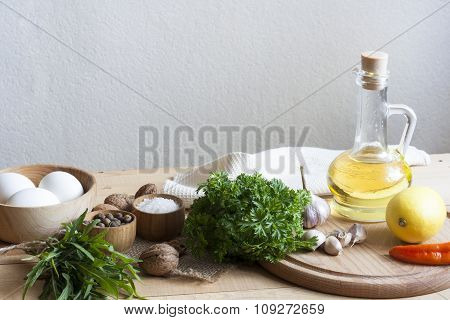 Food ingredients. Oil, eggs, garlic, limon, walnuts and herbs on wooden table. Wooden board and napk