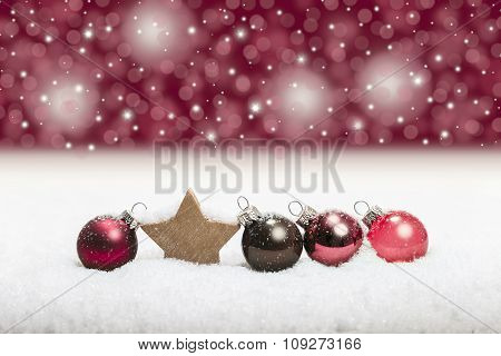 row of red christmas balls in snow