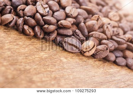 coffee grains on wooden background. light effect in the corner