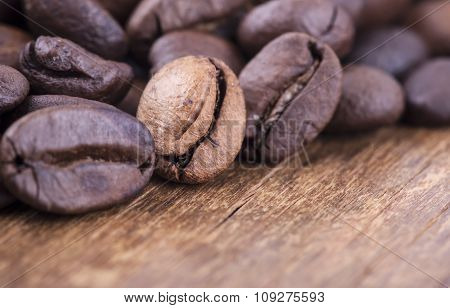 coffee grains on grunge wooden background closeup