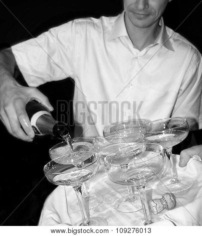 Barman pouring champagne in cristal glasses. Barmen with glasses and champagne