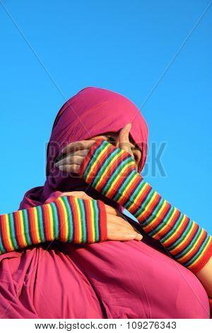 Muslim woman hiding behind hands. Hide concept