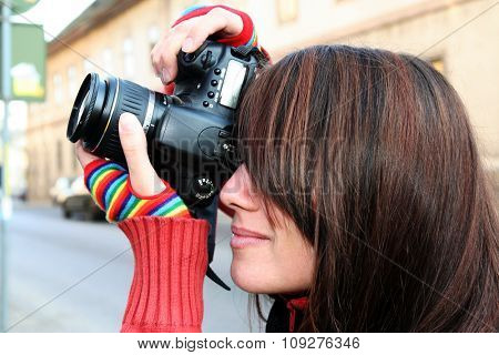 Young woman photographer and digital camera on the street