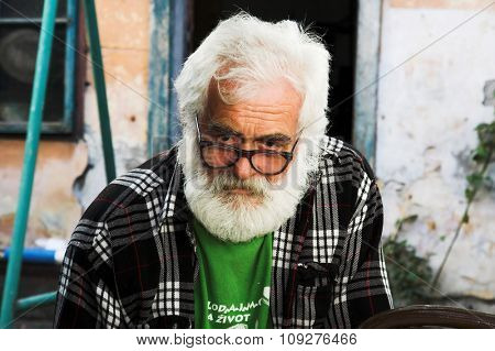 Old man portrait. Old man wearing glasses and grey beard.