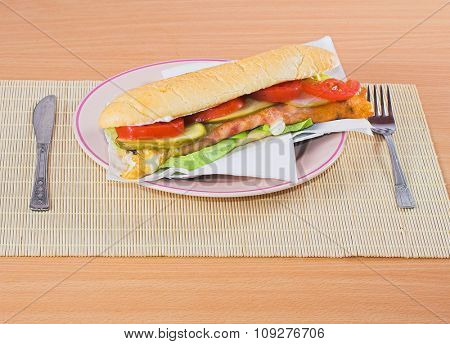 Tasty Fast food sandwich on plate. Table set with fork and knife
