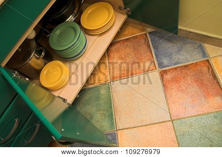 Open kitchen cupboard with dishes and plates. Colorful and lovely kitchen interior