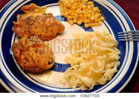 Served Chicken Thighs with Noodles and Corn
